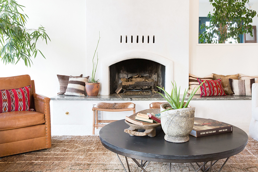 Interior family room designed by Nantucket Home with cowhide bench, kilim pillows, succulents and stucco fireplace